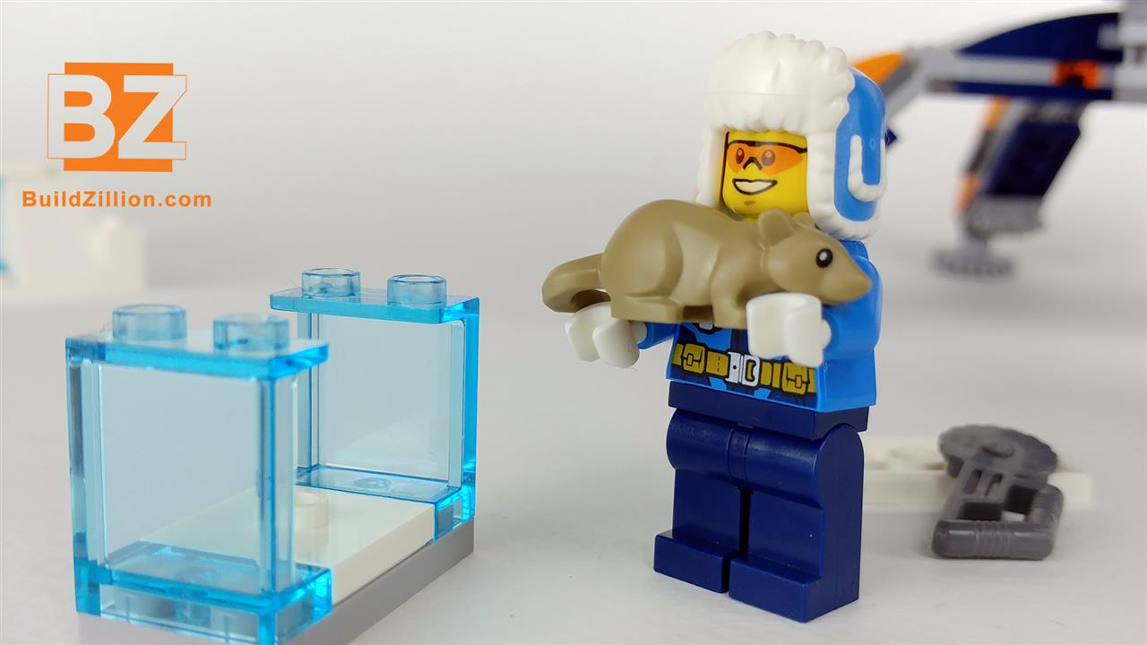 LEGO minifigure pickups the frozen rodent out of the ice block.